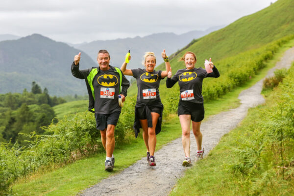 Three runners in fancy dress with thumbs up enjoying trails