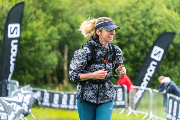 Happy female trail runner approaching finish line